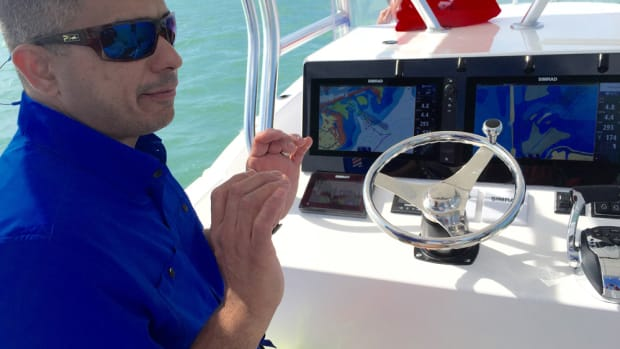 Tito Perez, a key account manager at Simrad, explains the multiple functions of a pair of the NSS Evo2 network navigation systems mounted on a Dusky 278 center console during a Navico press event in the Florida Keys.
