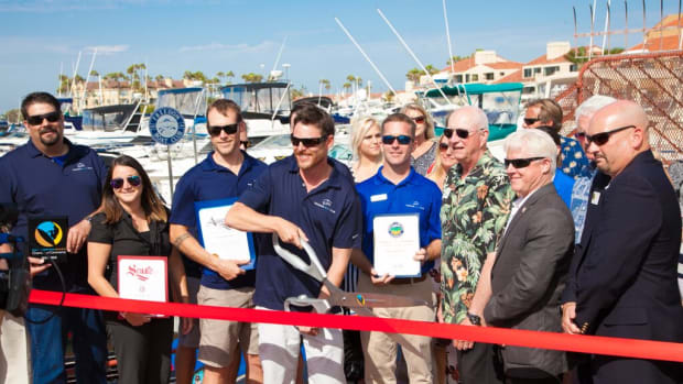 Andrew Hard, owner-operator of the Freedom Boat Club franchise in Huntington Beach, Calif., cuts the ribbon during grand opening festivities. Hard is flanked by Freedom Boat Club President and CEO John Giglio (right) and San Diego franchise owners Dan Hasbrouck and his wife, Jennifer (left), along with a group of regional dignitaries and VIPs.
