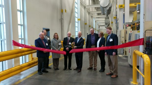 Mercury Marine president John Pfeifer cuts the ribbon for the commissioning of a 4,500-ton Buhler-Prince die-casting machine at the company's plant in Fond du Lac, Wis.