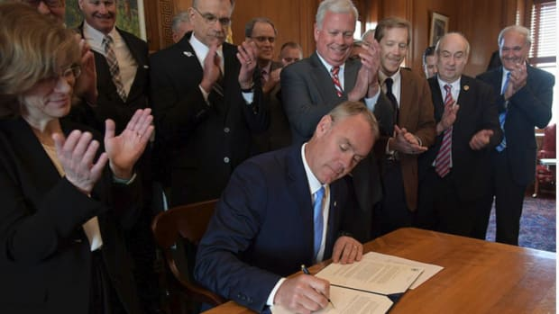 Interior Secretary Ryan Zinke (seated) is shown with National Marine Manufacturers Association president Thom Dammrich (center, right) and representatives of other outdoor groups.