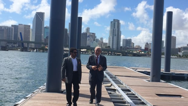 Mehmet Bayraktar (left), chairman and CEO of the Flagstone Property Group, walks with Miami Mayor Tomás Regalado on the completed piers at Island Gardens Deep Harbour.