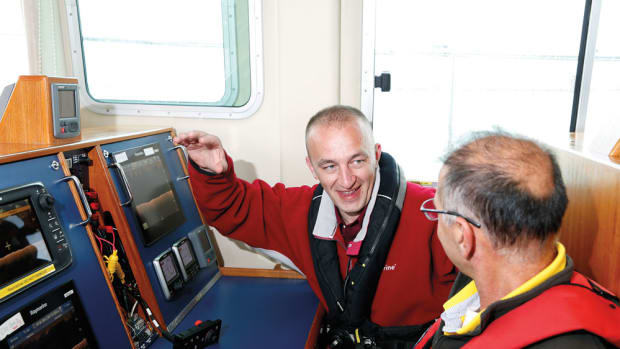 Raymarine product assurance engineer Drew Gorman (left) shows a journalist from Brazil the CHIRP DownVision sonar in one of six testing stations on the company's boat.