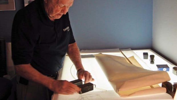 Dougherty is shown in a familiar pose, working at his drawing table.
