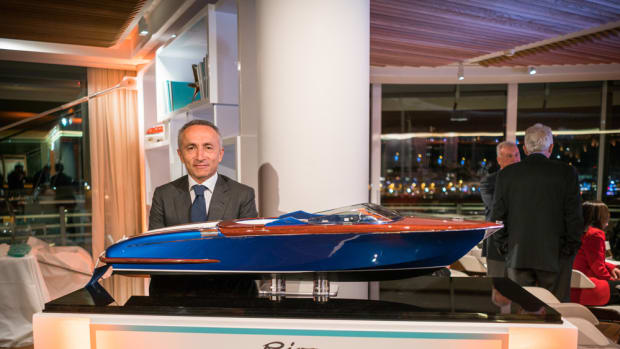 Ferretti Group CEO Alberto Galassi is shown with a model of the Aquariva Super that the group auctioned to raise money to support earthquake relief efforts in Italy.