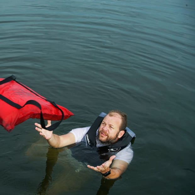 man-in-water-being-thrown-a-floatation-device