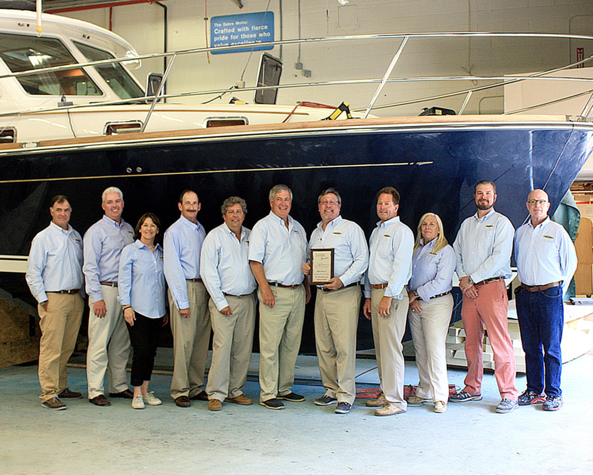 Sabre Yachts vice president of marketing and sales Bentley Collins gives Boston Yacht Sales owner/broker Michael Myers a plaque in recognition of the dealership's 20th year as a Sabre dealer. From left are Steve Moore; Andrew Savage; Rhonda Corey-Myers; Bruce Taymore; Bob Alliegro; Collins; Myers; Scott Lucas; Joyce Richards; Jonas Krisciunas; and Richard Parker.