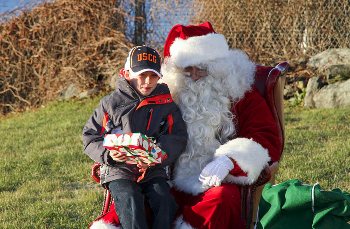 Santa Claus delivers a present during his 2014 visit to Coast Guard families in Rhode Island.