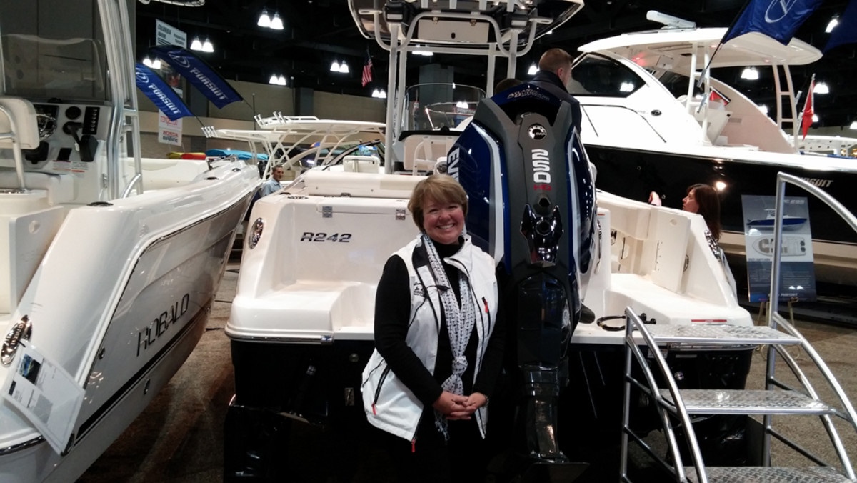 Kathleen Burns, executive director of the Connecticut Marine Trades Association, is shown with a Robalo boat powered by Evinrude, the show's official sponsor.