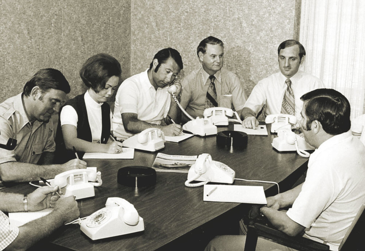 A young Eddie presides over a staff meeting.
