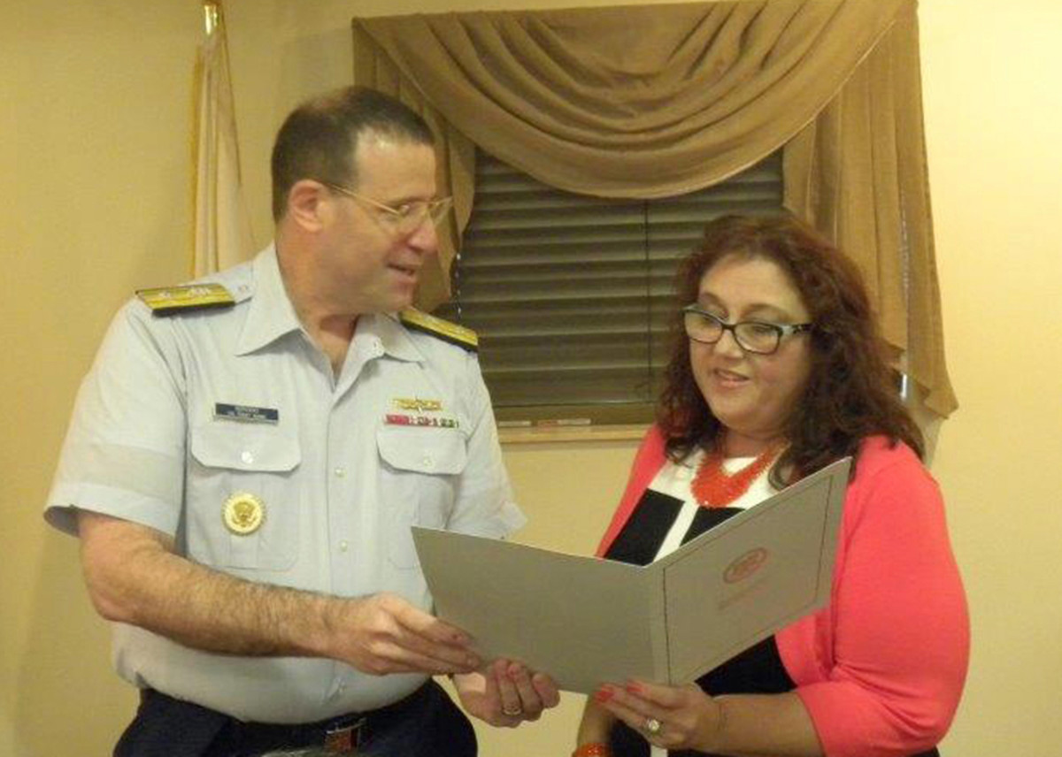 Amy Beavers, right, accepts the appointment from Rear Admiral Joseph Servidio.