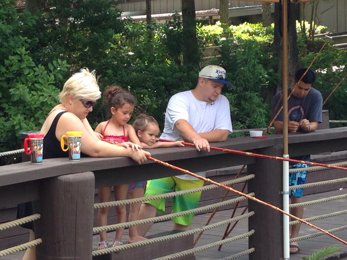 The children seem captivated as a family does some pole fishing at Disney's Fort Wilderness Resort.