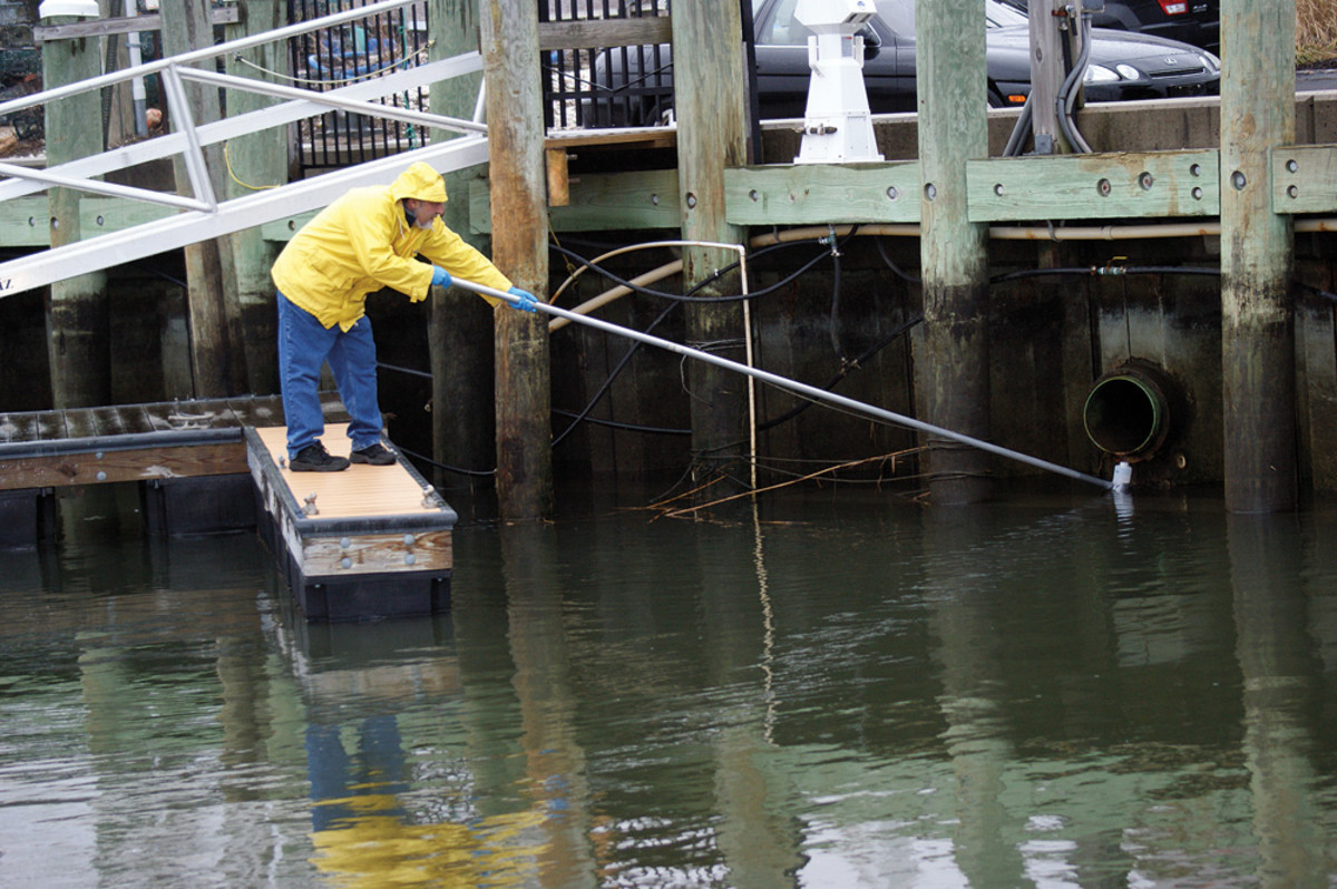 A marina employee performs storm water runoff testing in response to a reminder issued by software developed by environmental consultant Ted Sailer
