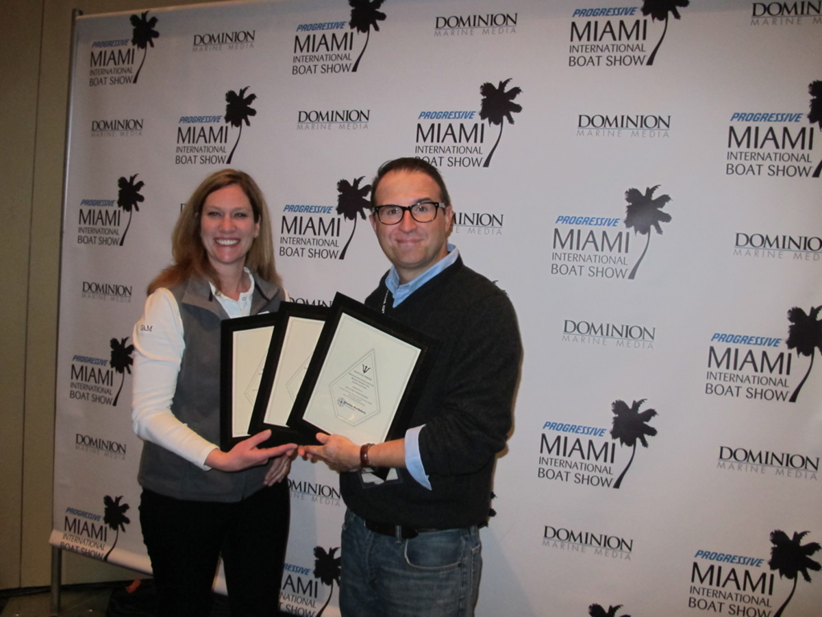 Markham Unlimited president Markham Cronin accepts three MMA Neptune Awards for Hell's Bay Boatworks during the Miami International Boat Show. He is shown with Neptune Awards co-chairwoman Cindy Pechous.
