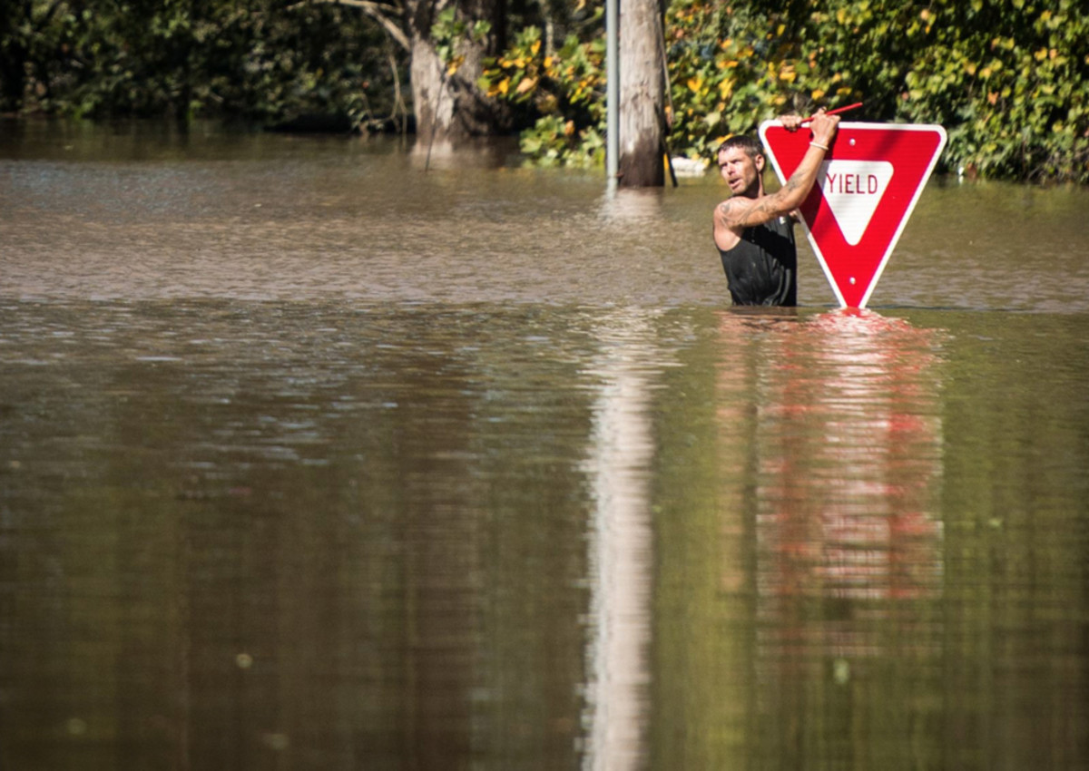 A man is shown holding on to a yield sign after trying to swim out to help a stranded truck driver at U.S. 301 and Tom Starling Road in Hope Mills, N.C., on Sunday. Both people were rescued. Fayetteville Observer photo by Andrew Craft.
