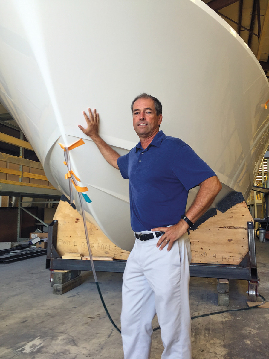 Bertram CEO Peter Truslow stands with hull No. 3 of the Bertram 35, being assembled at the new Tampa facility.