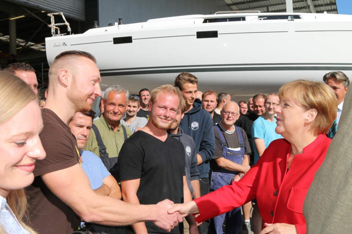 German Chancellor Angela Merkel greets workers at the Hanse Yachts AG shipyard.