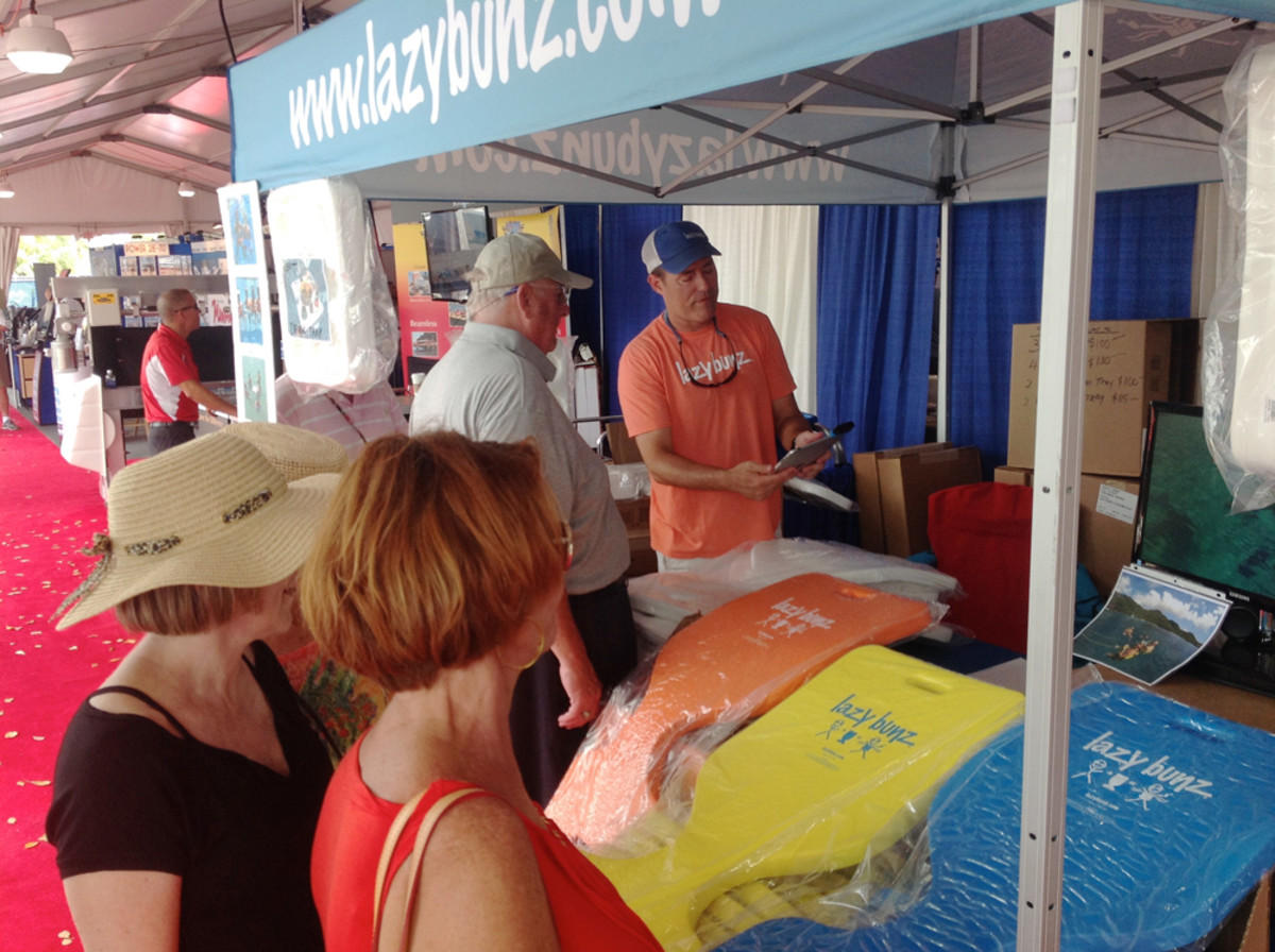 Chris Juall, founder of Lazy Bunz water floats, has been a vendor at the Suncoast show for three years. Here he finalizes a sale he made Sunday afternoon.