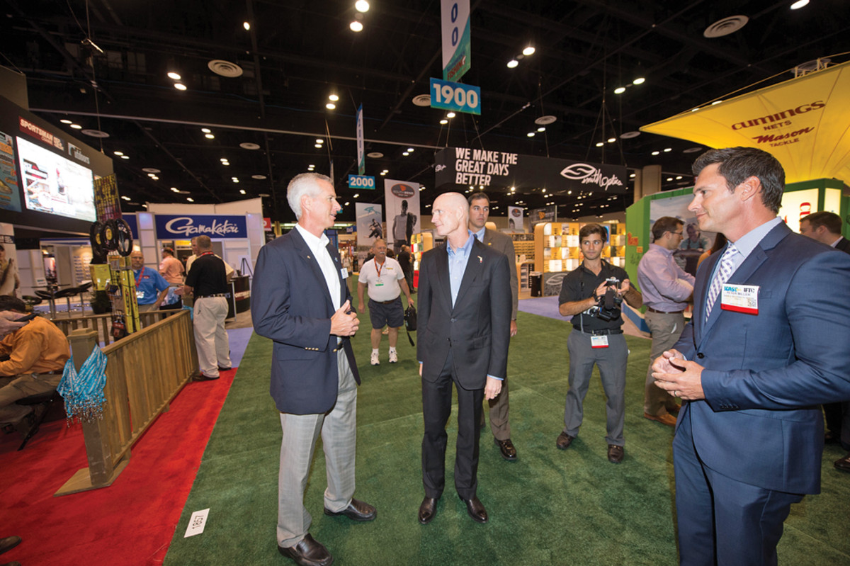Hughes (left) gives Florida Gov. Rick Scott a tour of the ICAST trade show floor in Orlando.