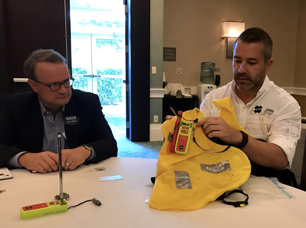Mikele D'Arcangelo of ACR demonstrates the company's new man-overboard device as Power & Motoryacht magazine's Jason Wood looks on.
