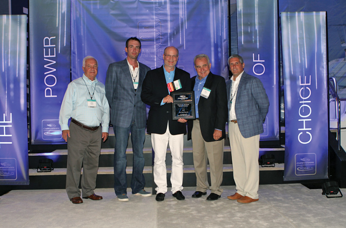 Briggs (center) received a Top 10 Dealer Award from Chaparral Boats last August in St. Petersburg, Fla. He is shown with Rick Hubbell (left), CEO of Marine Products Corp.; Bob Geiger, general manager of Wayzata Marine; Buck Pegg, founder of Chaparral Boats; and Ryan Good, regional sales manager at Chaparral.