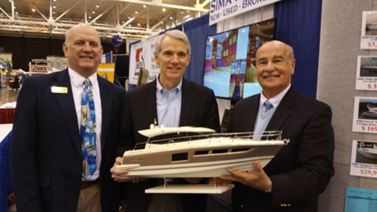 Sen. Rob Portman (center) holds a Prestige 500 model while visiting the Sima Marine exhibit in Cleveland. He's flanked by John Sima (left) and Norm Schultz who also addressed the LEMTA meeting.