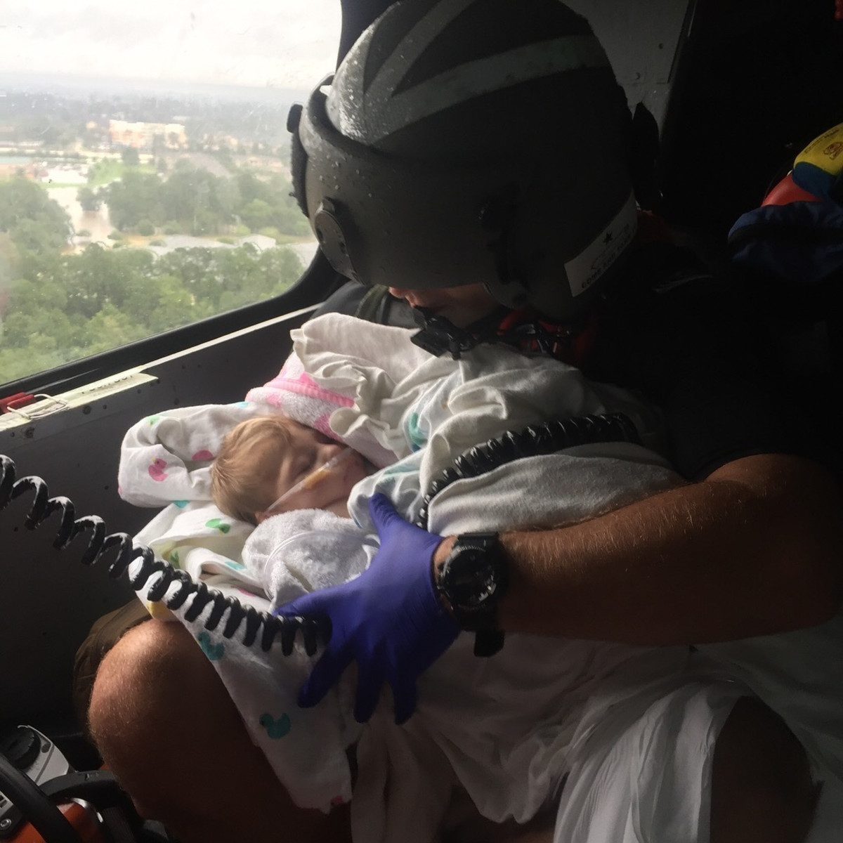 A Coast Guard aircrewman holds an infant during the aftermath of Hurricane Harvey