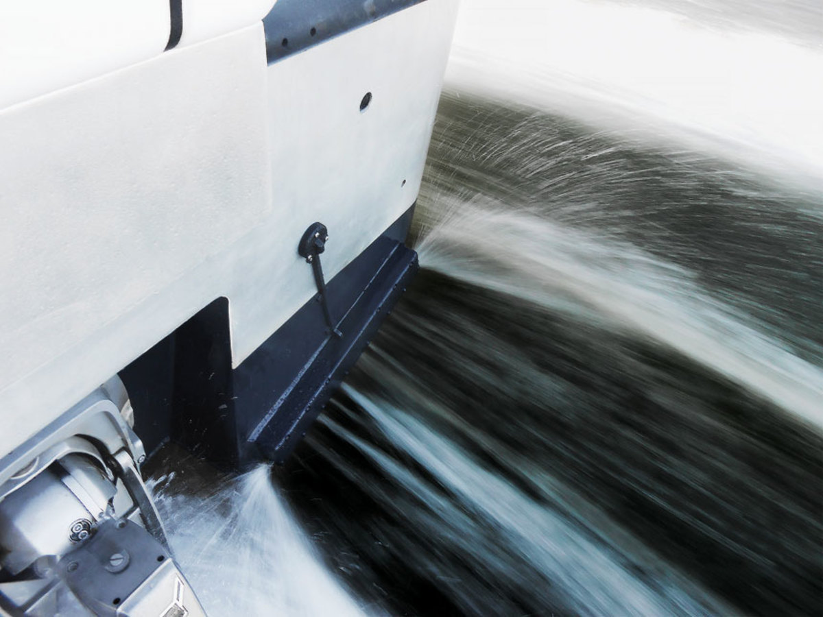 Water deflects off a Zipwake interceptor when it's lowered into the water to level the  boat's ride.