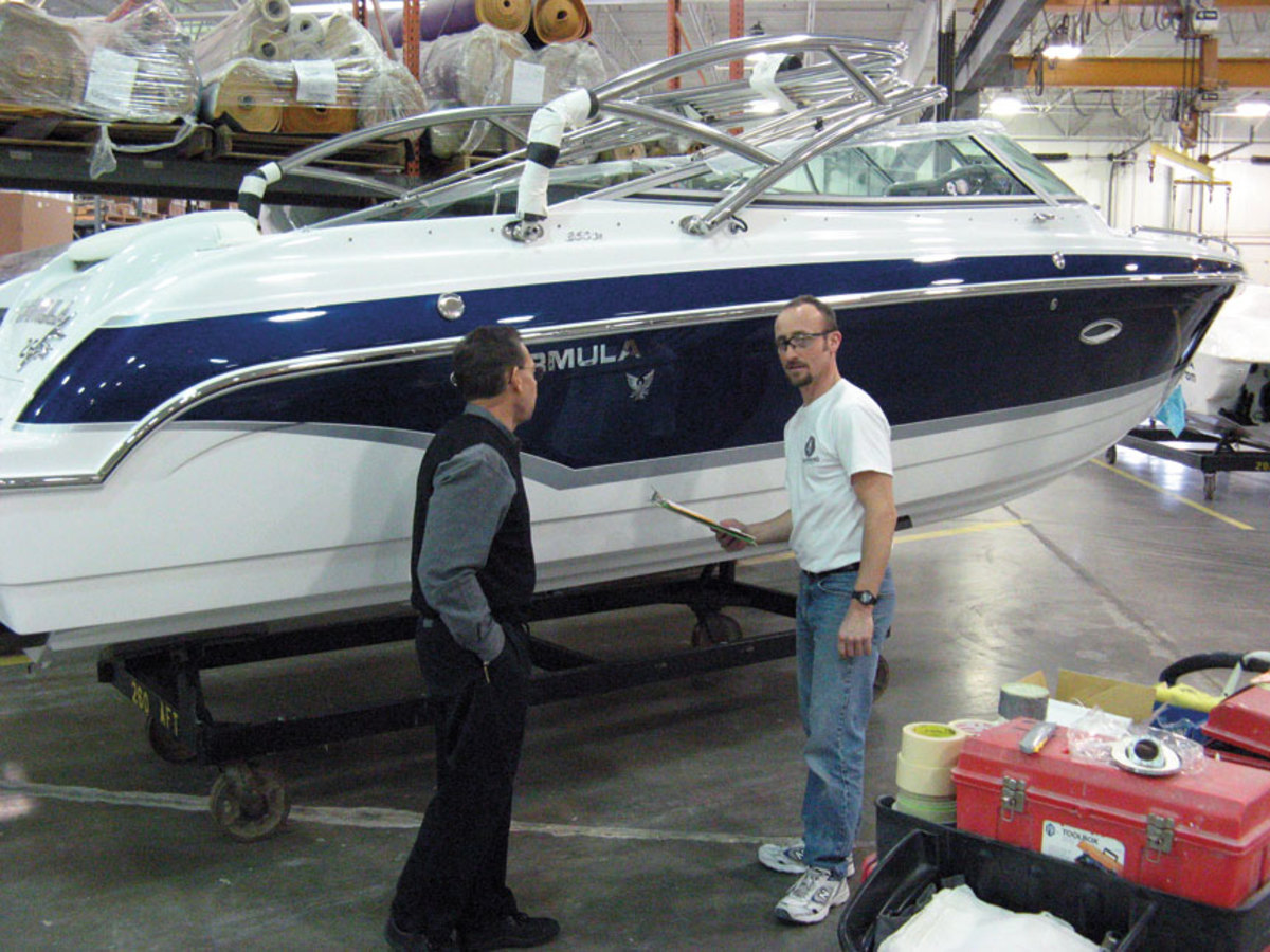Porter (left) checks on the progress of a Crossover bowrider on the factory floor. Notice how brightly the Imron paint shines.
