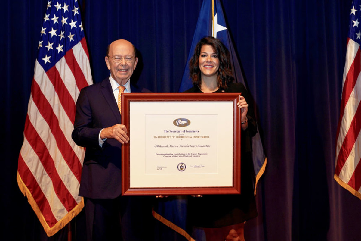 NMMA senior vice president of government and legal affairs, Nicole Vasilaros (right), accepts the E-Award from U.S. Secretary of Commerce Wilbur Ross.