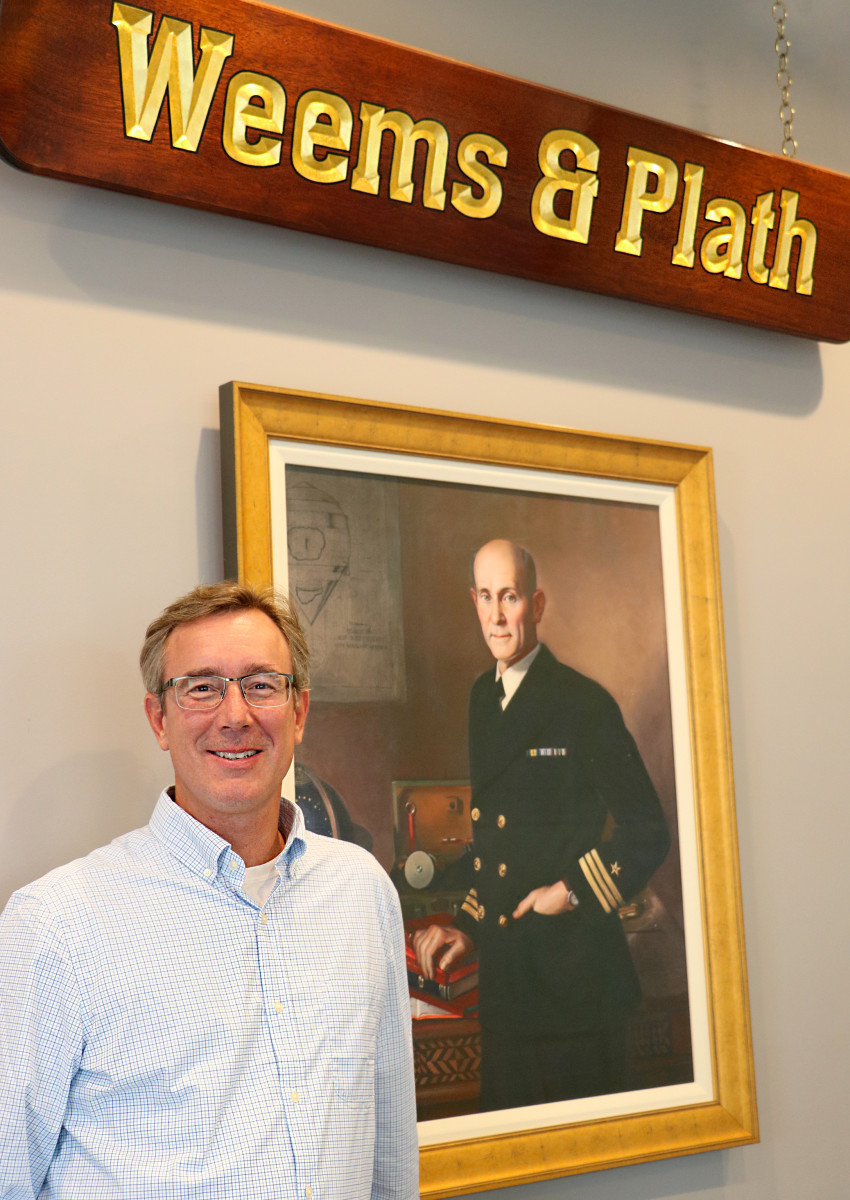 Michael Flanagan stands in front of a portrait of Weems & Plath's founder, Capt. P.V.H. Weems.