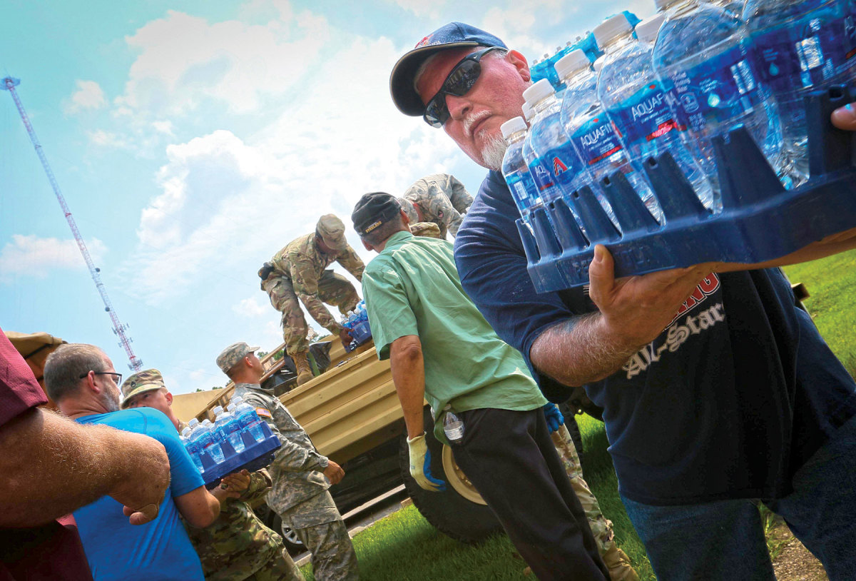 Volunteers helped load supplies, including these cases of badly needed bottled water.