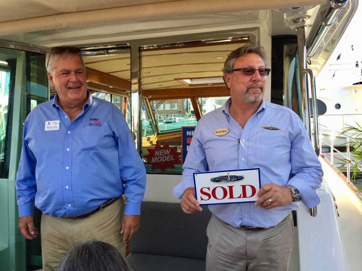 Michael Myers (right), of Boston Yacht Sales, holds a sold sign at the Newport International Boat Show after selling a Sabre 45SE. He is shown with Sabre Yachts sales and marketing vice president Bentley Collins.
