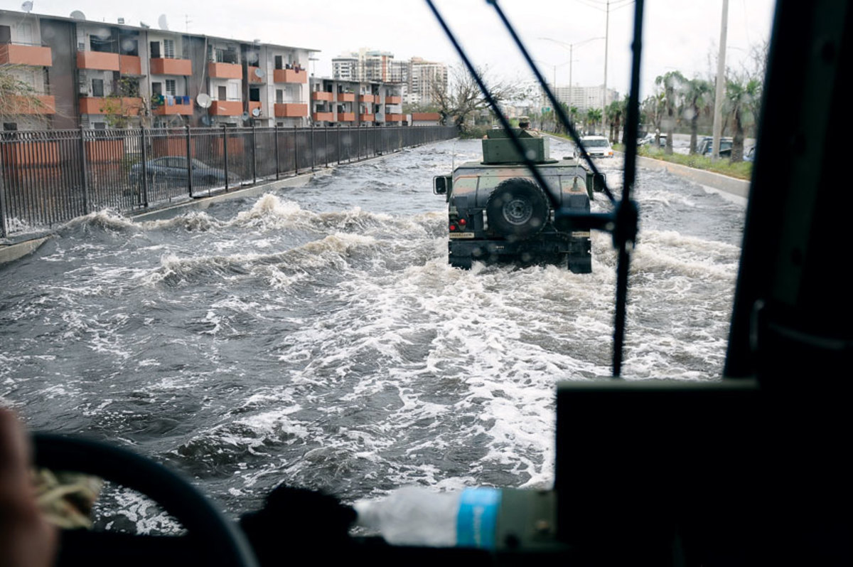 Citizen soldiers of the Puerto Rico National Guard patrol a flooded highway after Hurricane Maria struck the island.