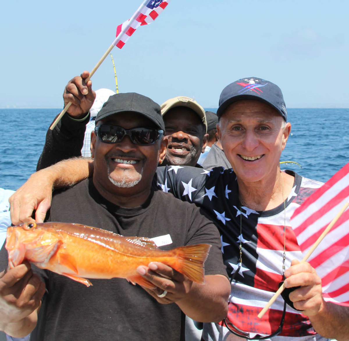 Volunteer Larry Brown celebrates a successful catch with veterans aboard the sportfishing boat Betty O. Doctors and recreational therapists say a fishing program for veterans is among the most popular recreational opportunities for them in Southern California.