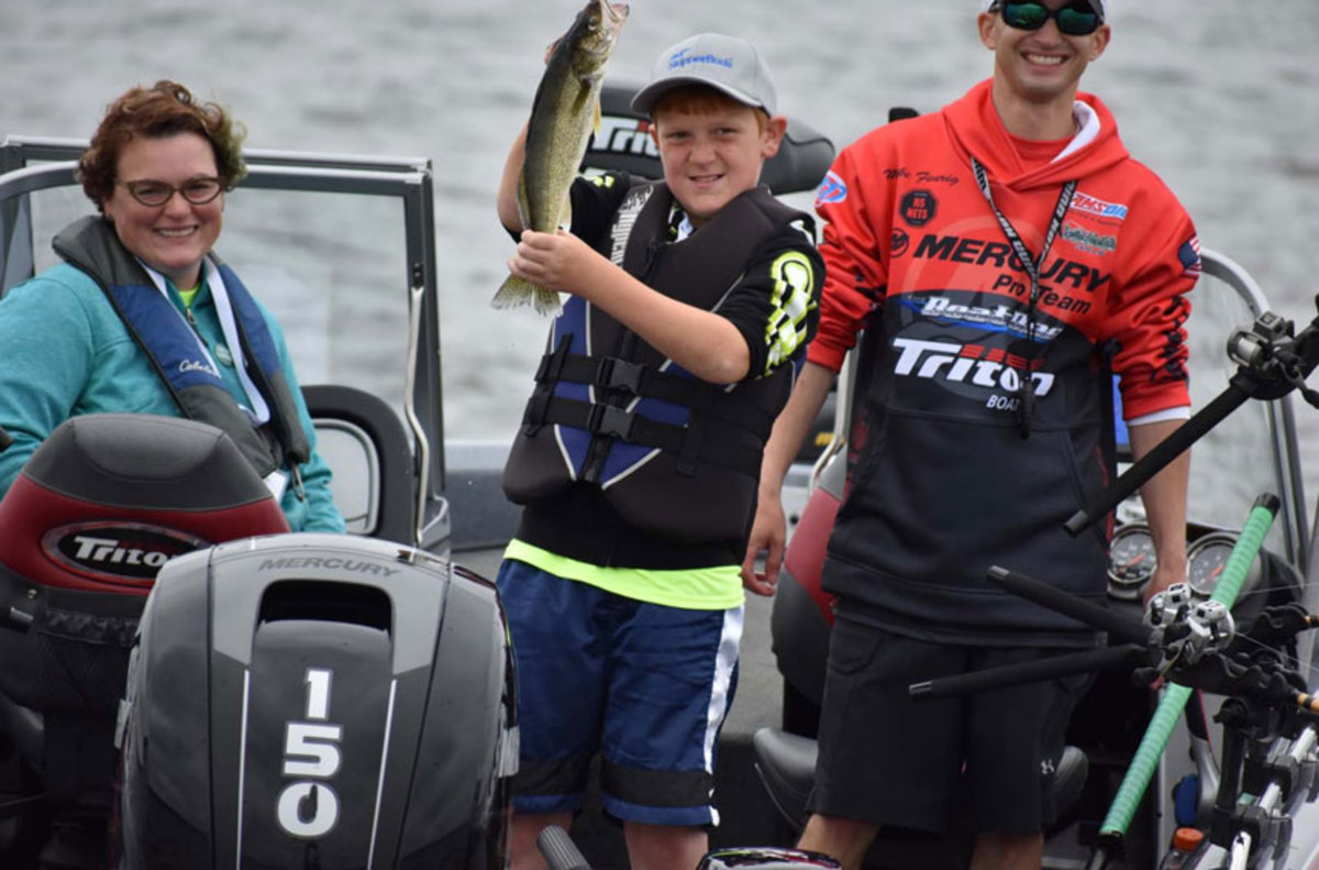 A participant in Tomorrow's Anglers Fish Quest holds up his catch.