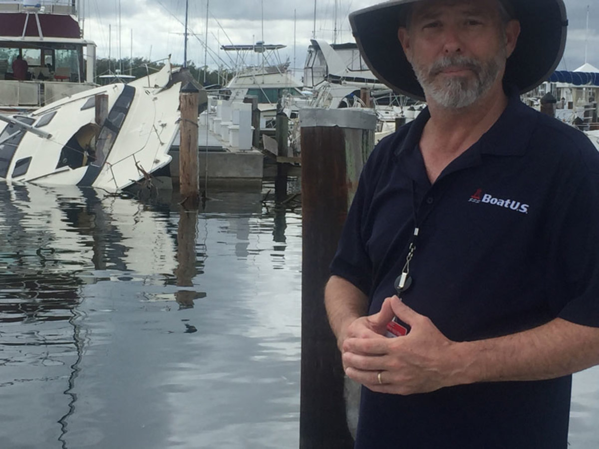 BoatUS public relations vice president Scott Croft is shown next to a BoatUS-insured catamaran that was badly damaged by Hurricane Irma at Dinner Key Marina.