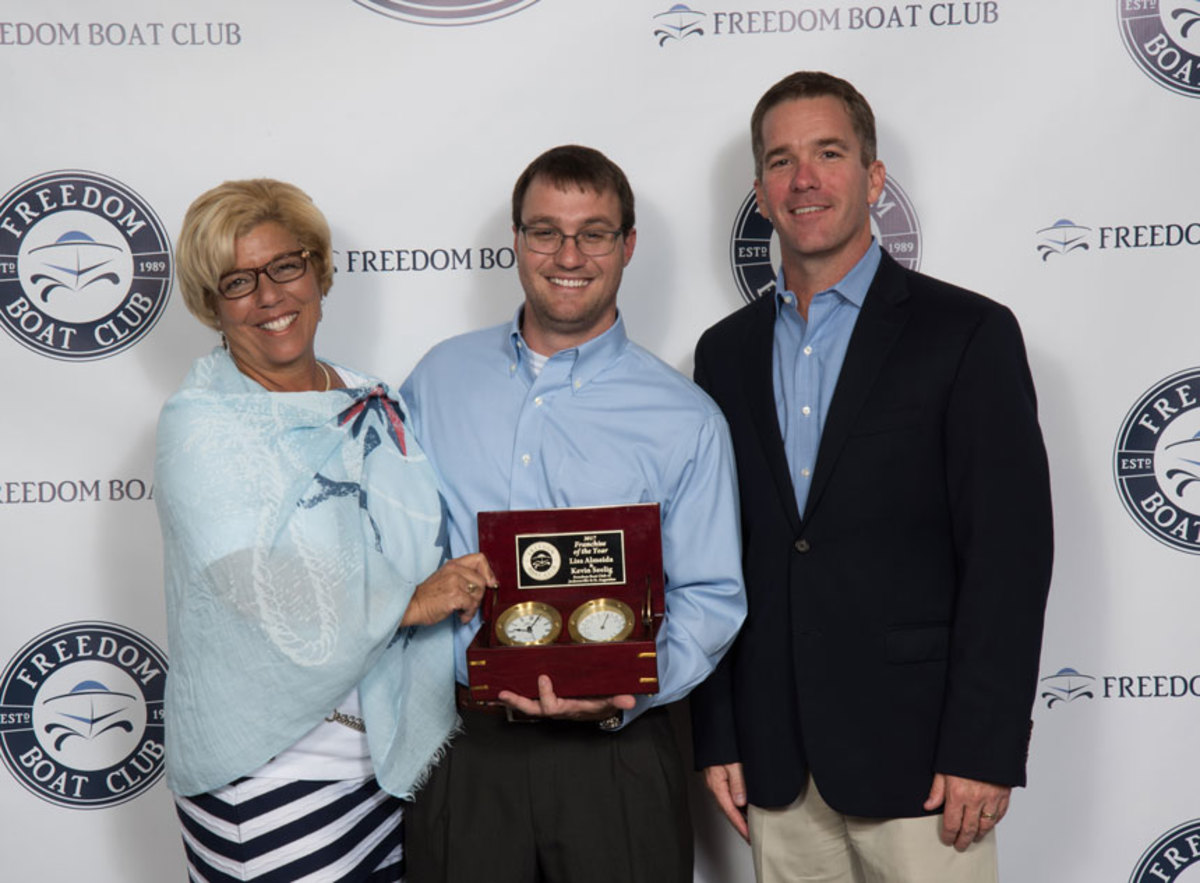 Lisa Almeida (left) and Kevin Seelig, of Freedom Boat Club of Jacksonville and St. Augustine, accept the Franchise of the Year award from company president and CEO John Giglio (right).