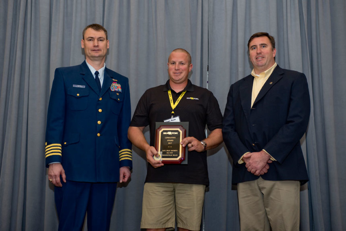 Sea Tow Services International honored Capt. Ryan Saporito (center) of Sea Tow Wrightsville Beach, N.C., for saving five people after their boat capsized. Also shown are Coast Guard Capt. William Carter (left), deputy director of incident management and preparedness policy, and Sea Tow CEO Capt. Joseph Frohnhoefer III.
