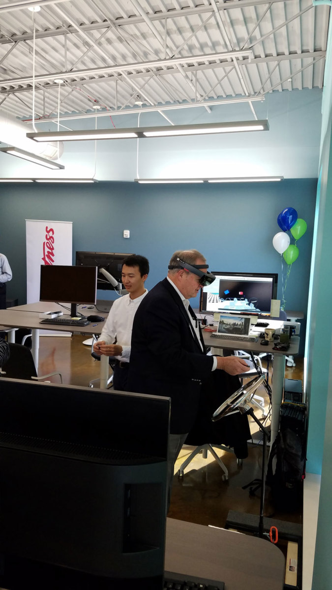Mark Schwabero, Brunswick's chairman and CEO, tries out a virtual technology headset during the grand opening.