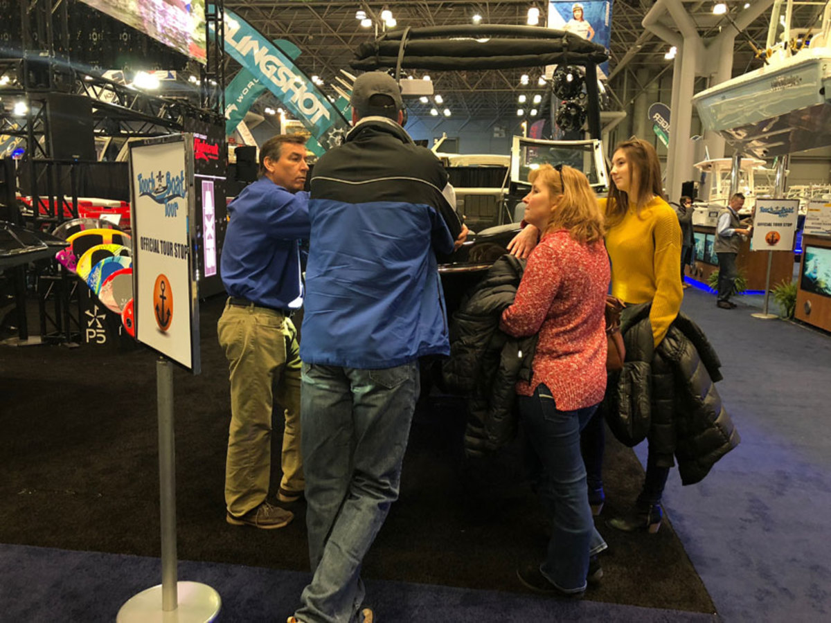 A family checks out a wakeboarding model at the New York Boat Show on Thursday. Dammrich told news outlet Cheddar about surf technology that allows wakeboarders to control the surf with a wristband.