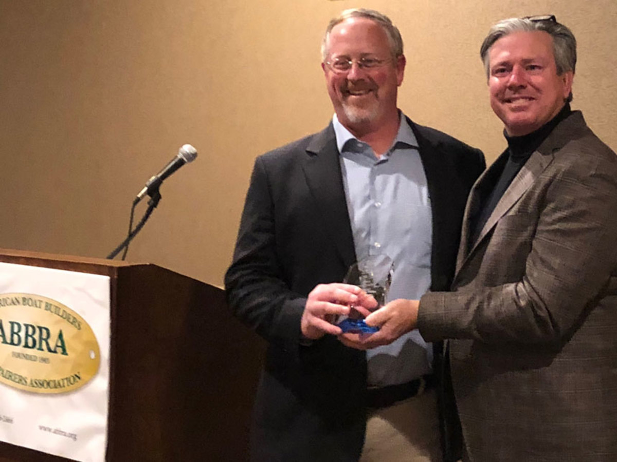 Tim Shields, VP of Service at Hinckley Yachts, Portsmouth, accepts the Boatyard of the Year from ABBRA Board President Ron Helbig at ABBRA's Annual Conference.