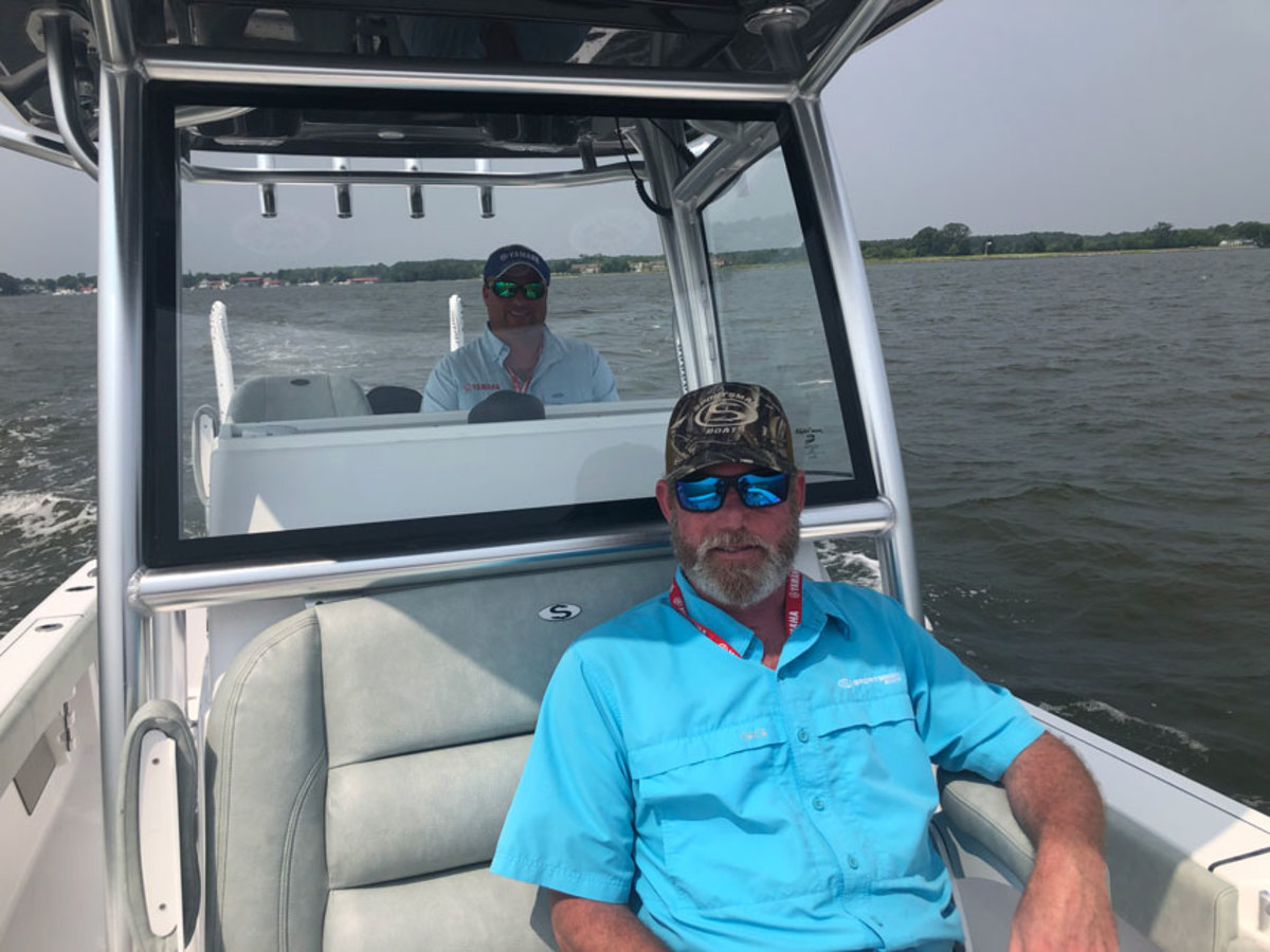 Sportsman Boats technical sales representative Will Coxe demonstrates the ride on the bow of its new 26-foot bay boat.