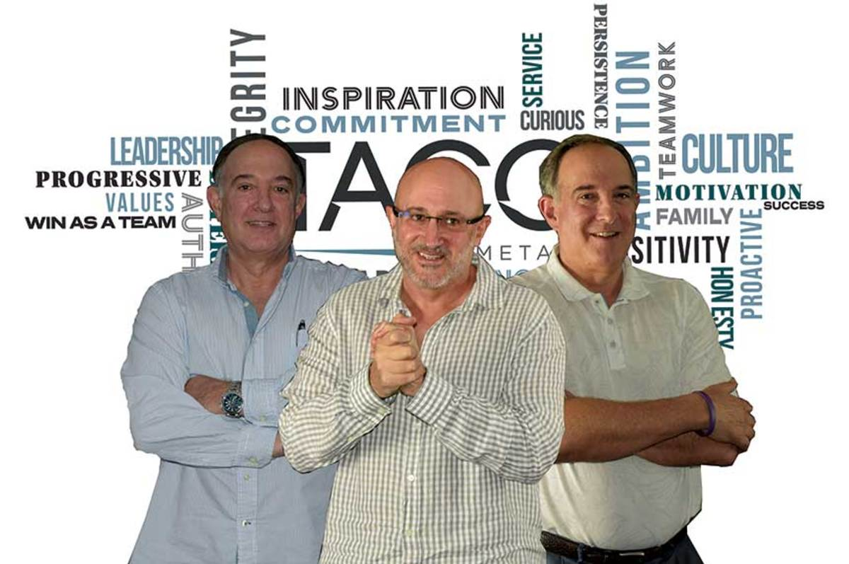 The Kushner brothers in front of the values wall at TACO's Miami headquarters