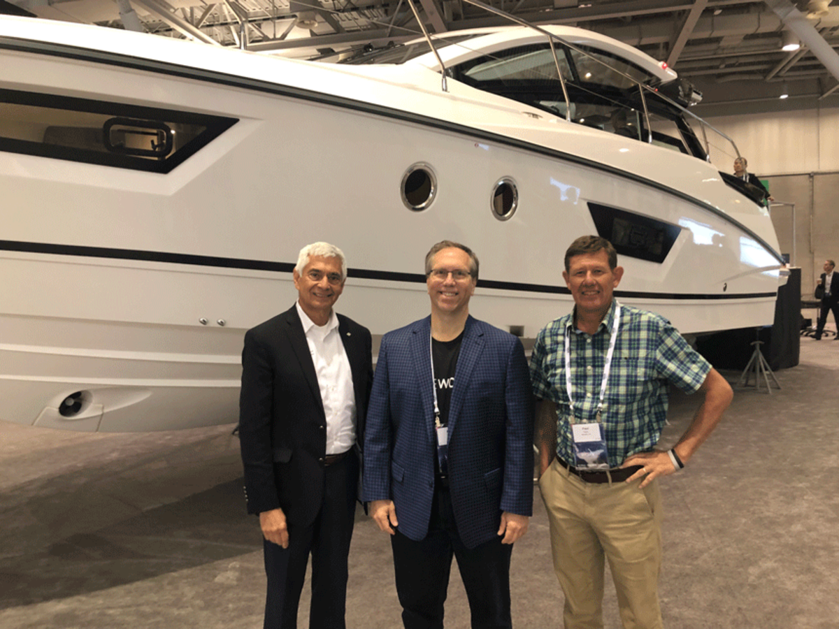 From left to right, Beneteau Americas CEO George Armendariz, PTC marketing vice president Mark Taber, and Paul Fenn with Take a Shot Media, stand in front of Beneteau's GT40 at LiveWorx in Boston.