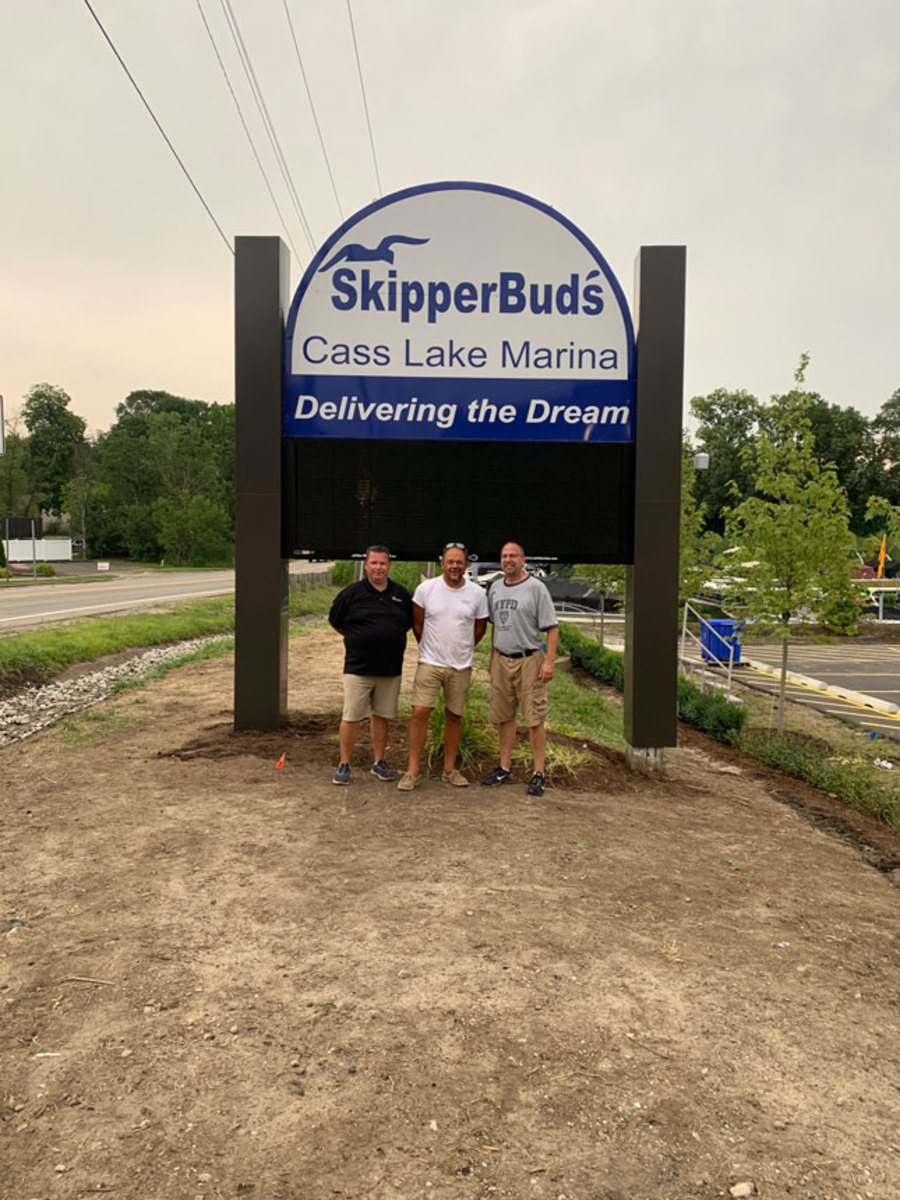 From left to right: SkipperBud's Cass Lake sales manager Chris Somers; development vice president Mark Ellerbrock; and regional vice president Trevis Burbach all stand in front of the new sign by Phillips Sign and Lighting Inc.