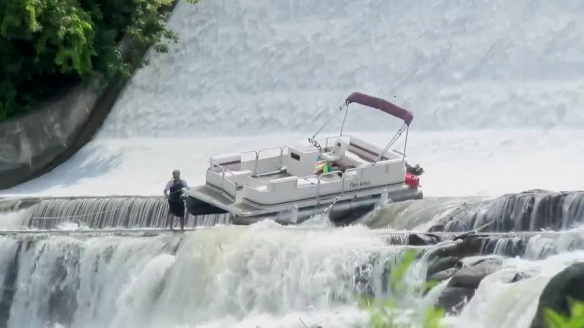 The pontoon boat dropped 50 feet before coming to rest on a lower section of the dam. Photo by CBS.