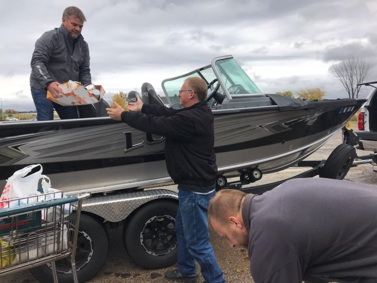 Mercury employees unload the boat full of donated food after hauling it to Fondy Food Pantry.