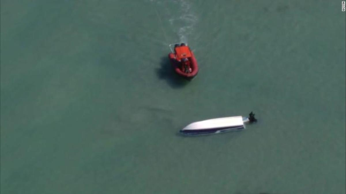 The Coast Guard was told that two boaters stayed with the overturned boat.