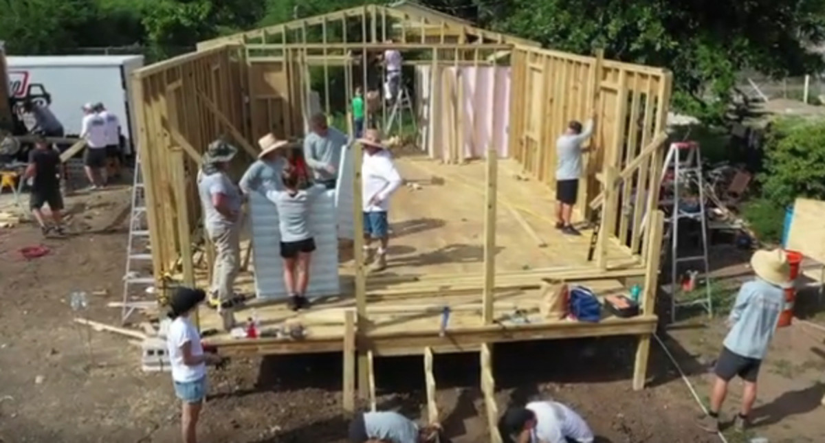 Volunteers rebuild a house destroyed by hurricanes in Puerto Rico.