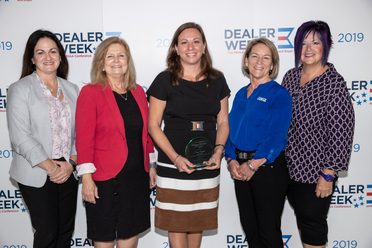 Sara Anghel (center) accepted the award from previous recipients at Dealer Week.